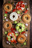 Delicious Bagel sandwiches with soft cheese, chorizo and vegetables Stock Photos