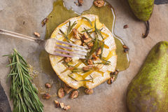 Delicious baked camembert with honey, walnuts, herbs and pears Stock Image