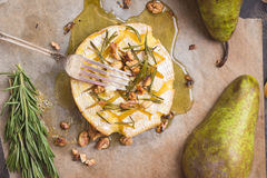 Delicious baked camembert with honey, walnuts, herbs and pears Royalty Free Stock Image