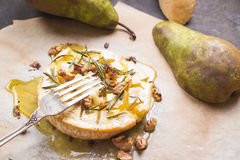 Delicious baked camembert with honey, walnuts, herbs and pears Royalty Free Stock Photos