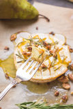 Delicious baked camembert with honey, walnuts, herbs and pears Stock Photo