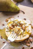 Delicious baked camembert with honey, walnuts, herbs and pears Stock Images