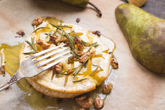 Delicious baked camembert with honey, walnuts, herbs and pears Royalty Free Stock Photo