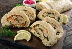Delicious baked ground fish fillet roulade. With greens, cheese and carrots cut in slices on dark wooden board, view from above, close-up Stock Image