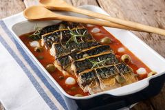 Delicious baked mackerel with capers and olives in tomato sauce. Close-up on a table in a baking dish. horizontal Royalty Free Stock Photos