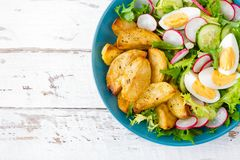 Delicious baked potato, boiled egg and fresh vegetable salad of lettuce, cucumber and radish. Summer menu for detox diet. Top view stock images
