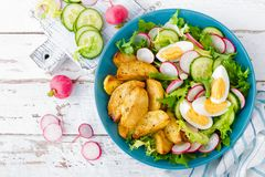 Delicious baked potato, boiled egg and fresh vegetable salad of lettuce, cucumber and radish. Summer menu for detox diet. Top view stock image