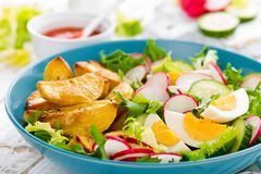 Delicious baked potato, boiled egg and fresh vegetable salad of lettuce, cucumber and radish. Summer menu for detox diet. Top view. Delicious baked potato royalty free stock images