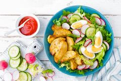 Delicious baked potato, boiled egg and fresh vegetable salad of lettuce, cucumber and radish. Summer menu for detox diet. Top view royalty free stock photos