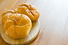 Delicious baking round buns made on a wooden table. Royalty Free Stock Photography
