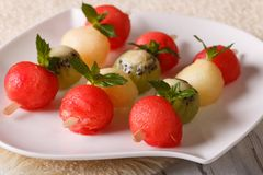 Delicious balls of watermelon, kiwi and melon on skewers close-u Stock Photos
