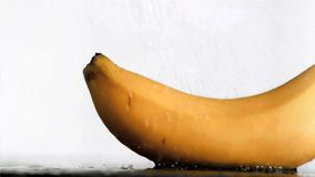 Delicious banana in super slow motion receiving water