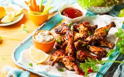 Delicious barbecue chicken wings. With two sauces and carrot with celery on vintage serving tray Royalty Free Stock Images