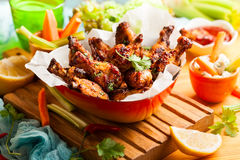 Delicious barbecue chicken wings. With two sauces and carrot with celery in vintage serving bowl Stock Photo