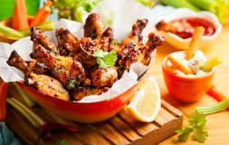 Delicious barbecue chicken wings. With two sauces and carrot with celery in vintage serving bowl Royalty Free Stock Photos