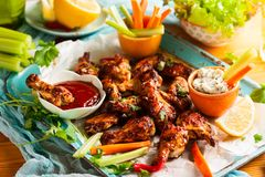 Delicious barbecue chicken wings. With two sauces and carrot with celery on vintage serving tray Royalty Free Stock Photography