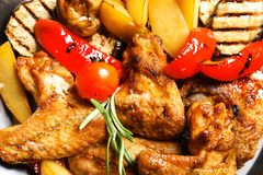 Delicious barbecued chicken wings with garnish served in wok stock image