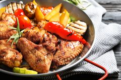 Delicious barbecued chicken wings with garnish served in wok royalty free stock image