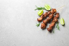 Delicious barbecued meat with rosemary and lime on grey background, top view. stock image