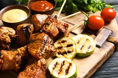 Delicious barbecued meat served with garnish and sauces. On wooden board, closeup stock photos
