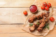 Delicious barbecued meat served with sauce and garnish on wooden background, top view stock images