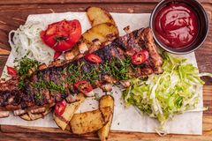 Delicious barbecued ribs seasoned with fresh herbs, cabbage salad, backed potato on an old rustic wooden chopping board. Delicious barbecued ribs seasoned with a stock photo