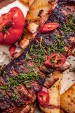 Delicious barbecued ribs seasoned with fresh herbs, cabbage salad, backed potato on an old rustic wooden chopping board. Delicious barbecued ribs seasoned with a royalty free stock image
