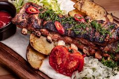 Delicious barbecued ribs seasoned with fresh herbs, cabbage salad, backed potato on an old rustic wooden chopping board. Delicious barbecued ribs seasoned with a stock image