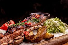 Delicious barbecued ribs seasoned with fresh herbs, cabbage salad, backed potato on an old rustic wooden chopping board stock photos