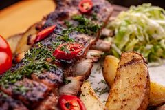 Delicious barbecued ribs seasoned with fresh herbs, cabbage salad, backed potato on an old rustic wooden chopping board stock images