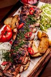 Delicious barbecued ribs seasoned with fresh herbs, cabbage salad, backed potato on an old rustic wooden chopping board. Delicious barbecued ribs seasoned with a stock photos