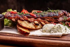 Delicious barbecued ribs seasoned with fresh herbs, cabbage salad, backed potato on an old rustic wooden chopping board stock photography