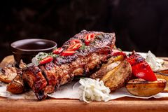 Delicious barbecued ribs seasoned with fresh herbs, cabbage salad, backed potato on an old rustic wooden chopping board royalty free stock image