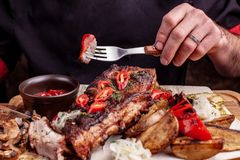 Delicious barbecued ribs seasoned with fresh herbs, cabbage salad, backed potato on an old rustic wooden chopping board. Delicious barbecued ribs seasoned with a royalty free stock photography