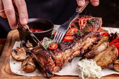 Delicious barbecued ribs seasoned with fresh herbs, cabbage salad, backed potato on an old rustic wooden chopping board. Delicious barbecued ribs seasoned with a royalty free stock photo