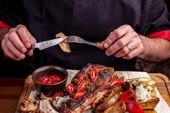 Delicious barbecued ribs seasoned with fresh herbs, cabbage salad, backed potato on an old rustic wooden chopping board. Delicious barbecued ribs seasoned with a stock images