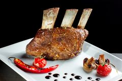 Delicious barbecued ribs seasoned served with mushrooms on a white plate. Clouse up royalty free stock image