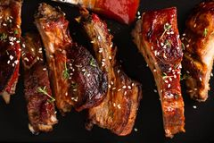 Delicious barbecued ribs seasoned with a spicy basting sauce. lose-up, copy space. Delicious barbecued ribs seasoned with a spicy basting sauce and served with royalty free stock photo