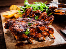 Delicious barbecued ribs. Seasoned with a spicy basting sauce and served with chopped fresh herbs on an old rustic wooden chopping board in a country kitchen stock images