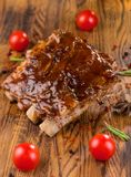 Delicious barbecued ribs seasoned with a spicy basting sauce and served with chopped fresh vegetables on an old rustic stock photography