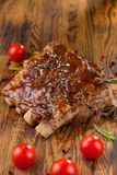 Delicious barbecued ribs seasoned with a spicy basting sauce and served with chopped fresh vegetables on an old rustic royalty free stock photo