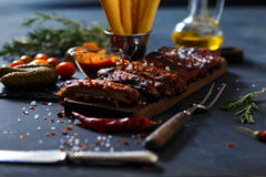 Delicious barbecued ribs seasoned with a spicy basting sauce and served with chopped. Fresh vegetables on an old rustic wooden chopping board in a country Royalty Free Stock Image