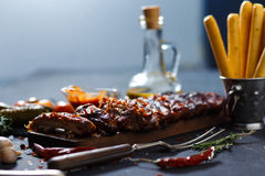Delicious barbecued ribs seasoned with a spicy basting sauce and served with chopped. Fresh vegetables on an old rustic wooden chopping board in a country Royalty Free Stock Photo