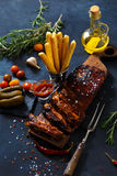 Delicious barbecued ribs seasoned with a spicy basting sauce and served with chopped. Fresh vegetables on an old rustic wooden chopping board in a country Royalty Free Stock Photos