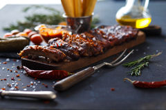 Delicious barbecued ribs seasoned with a spicy basting sauce and served with chopped. Fresh vegetables on an old rustic wooden chopping board in a country Stock Photo