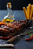 Delicious barbecued ribs seasoned with a spicy basting sauce and served with chopped. Fresh vegetables on an old rustic wooden chopping board in a country Stock Photos