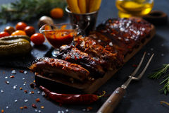 Delicious barbecued ribs seasoned with a spicy basting sauce and served with chopped. Fresh vegetables on an old rustic wooden chopping board in a country Royalty Free Stock Photography