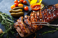 Delicious barbecued ribs seasoned with a spicy basting sauce and served with chopped. Fresh vegetables on an old rustic wooden chopping board in a country Stock Photography