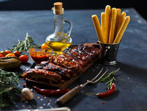 Delicious barbecued ribs seasoned with a spicy basting sauce and served with chopped. Fresh vegetables on an old rustic wooden chopping board in a country Stock Images