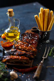 Delicious barbecued ribs seasoned with a spicy basting sauce and served with chopped. Fresh vegetables on an old rustic wooden chopping board in a country Stock Image